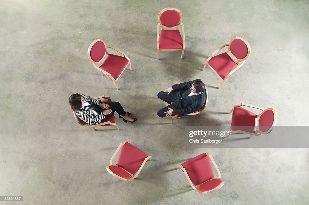 man and woman in a circle of chairs : Stock-Foto