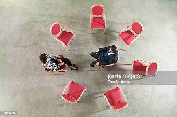 man and woman in a circle of chairs