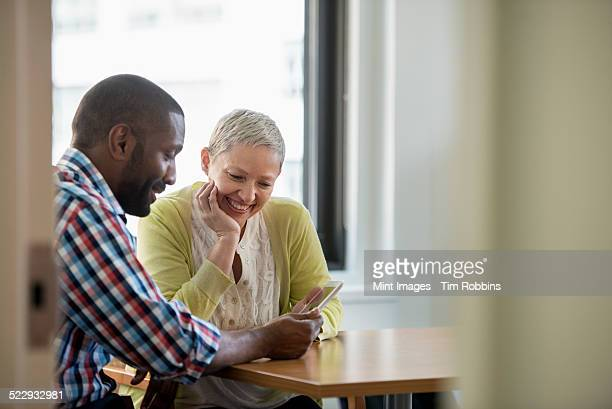 A man and woman in an office, sharing a digital tablet.
