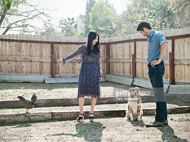 Man and woman in backyard with dog and chicken
