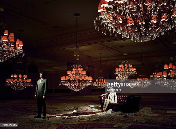 Man and woman in ball room, newspaper on the floor
