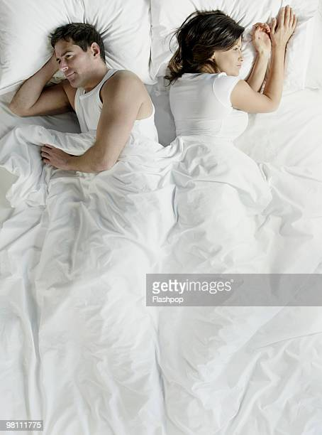 Man and woman in bed facing away from each other