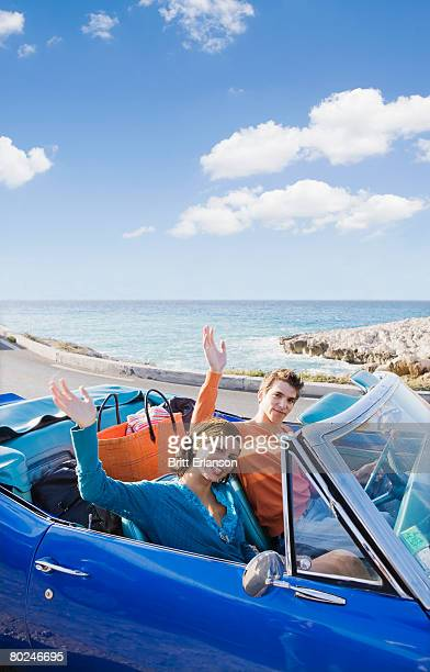 Man and woman in car by sea waving.