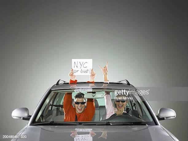 Man and woman in car, man holding 'NYC or bust' sign out sun roof