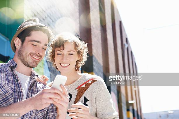 man and woman in city looking a mobile