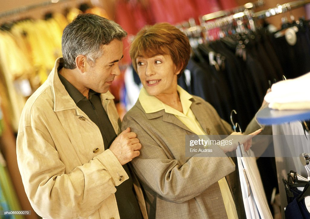 Man and woman in clothing store, waist up. : Stockfoto