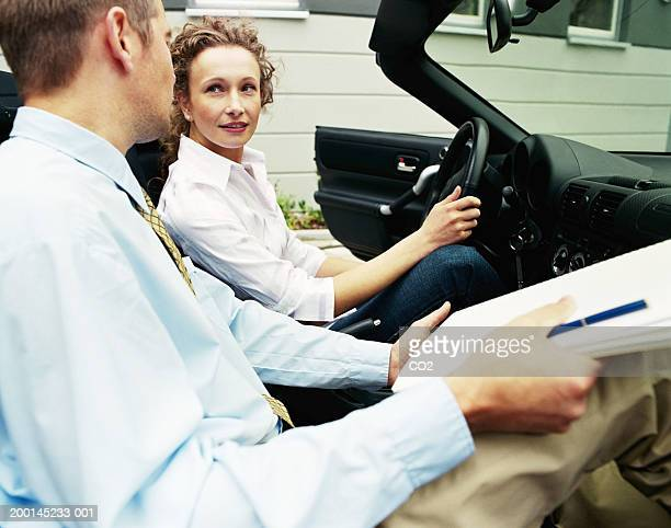 Man and woman  in convertible car, woman in driver's seat