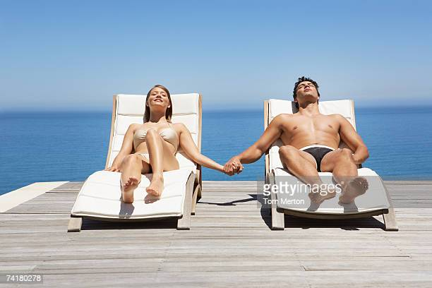 Man and woman in deck chairs sunbathing holding hands