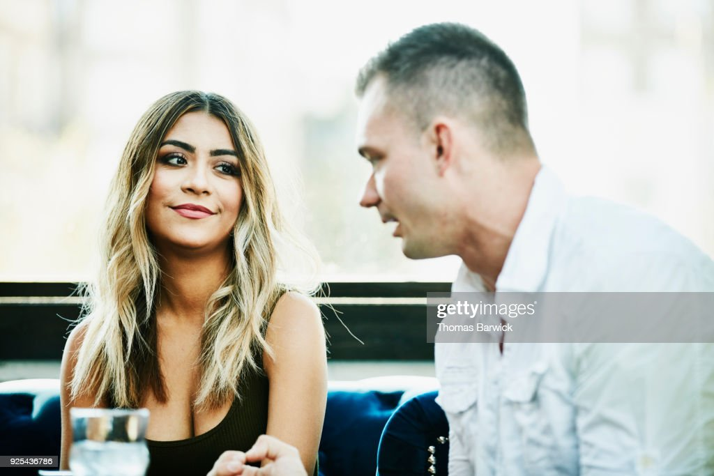 Man and woman in discussion while sharing drinks in bar : Stock Photo