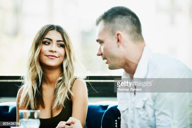 man and woman in discussion while sharing drinks in bar - flirting stock pictures, royalty-free photos & images