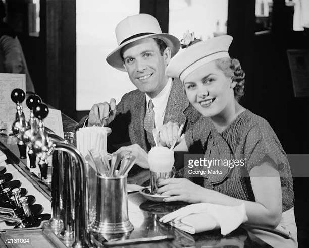 Hombre y mujer en el sombrero elegante beber gaseosa con helado