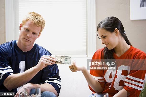 Man and woman in football jerseys handing woman money