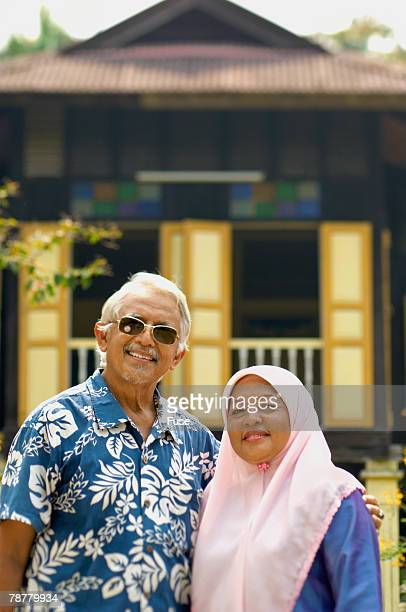 Man and Woman in Front of Malay House