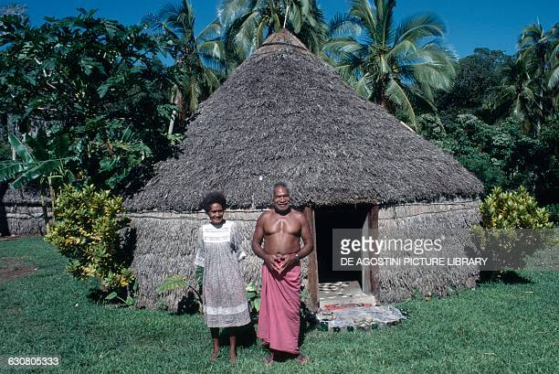 A man and woman in front of traditional housing Lifou Island Loyalty Islands New Caledonia French Overseas Territory