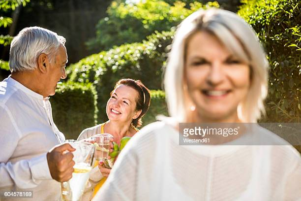 Man and woman in garden with smiling woman in foreground