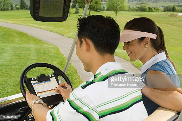 Man and woman in golf cart with scorecard