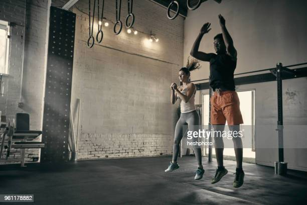 man and woman in gym jumping in mid air - heshphoto photos et images de collection