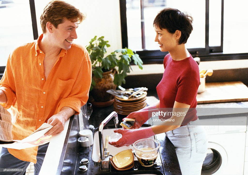Man and woman in kitchen, looking at each other over counter, woman washing dishes : Stockfoto