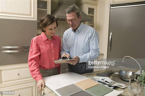 Man and woman in kitchen looking at tile samples