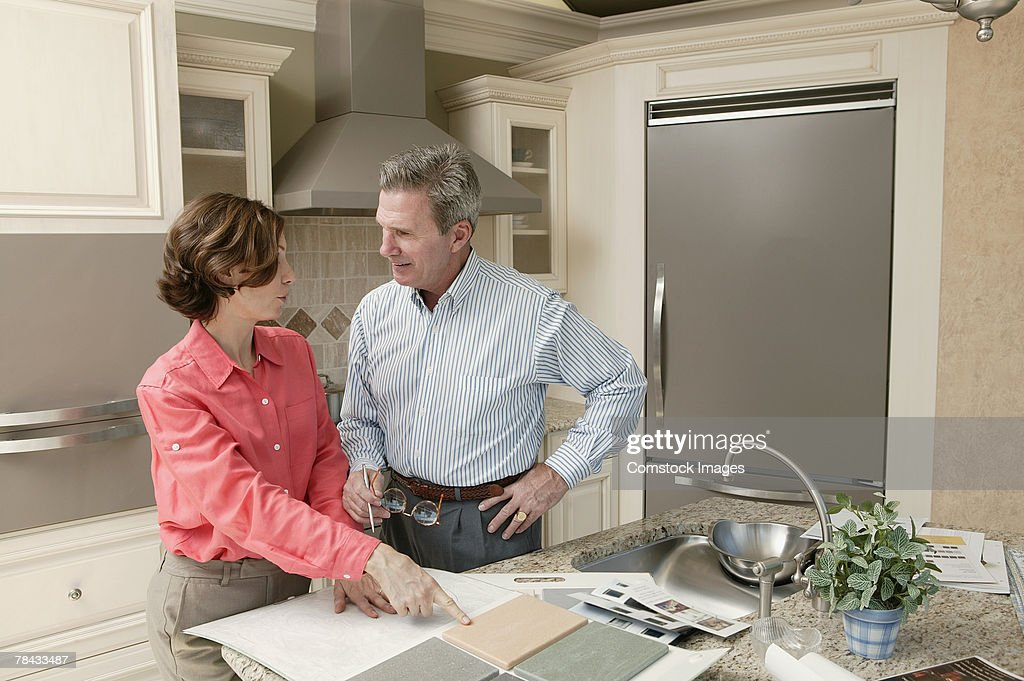 Man and woman in kitchen with tile samples : Stockfoto