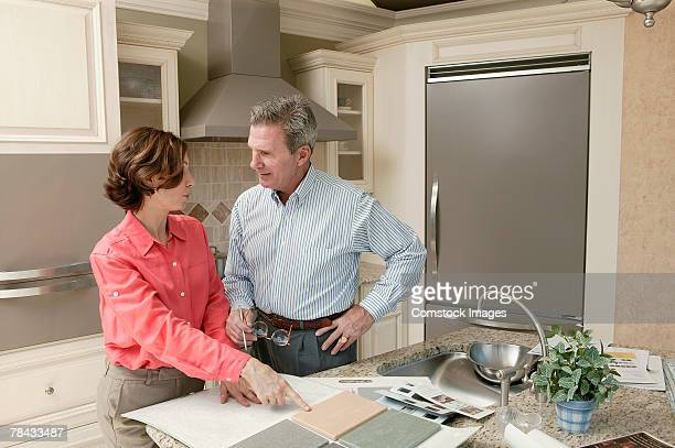 Man and woman in kitchen with tile samples