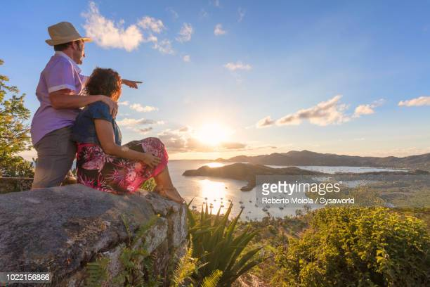 Man and woman in love look toward the bay and English Harbor from hills of Shirley Heights, Antigua