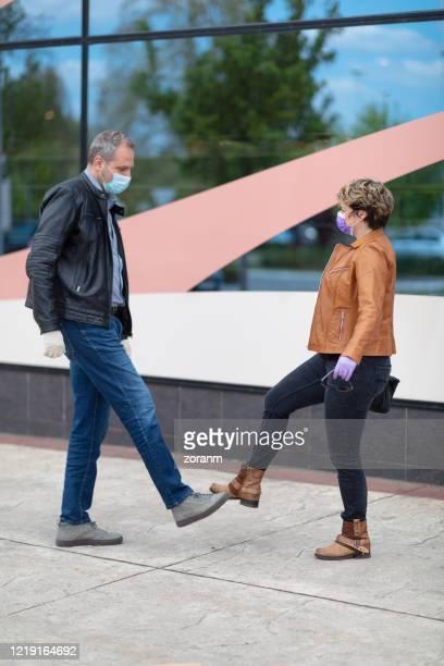 man en vrouw in masker en handschoenen die met voetschudden begroeten - uithoudingsvermogen stockfoto's en -beelden