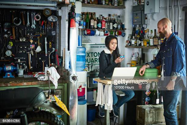 Man and woman in motorcycle workshop.