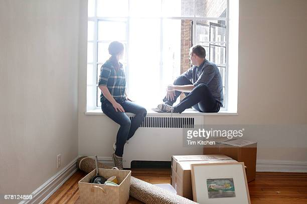 Man and woman in new apartment, looking out window
