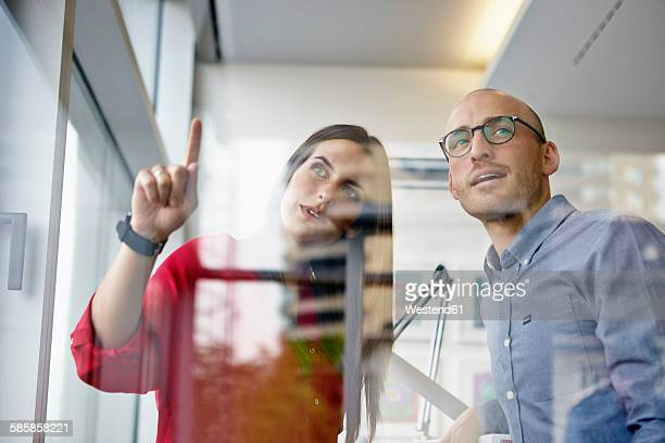 Man and woman in office discussing behind glass pane