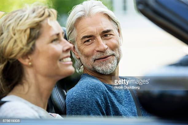 Man and Woman in open car laughing