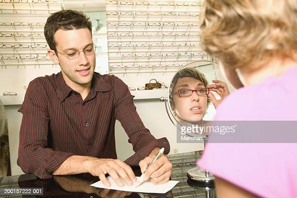 Man and woman in optcians, woman trying on glasses in front of mirror