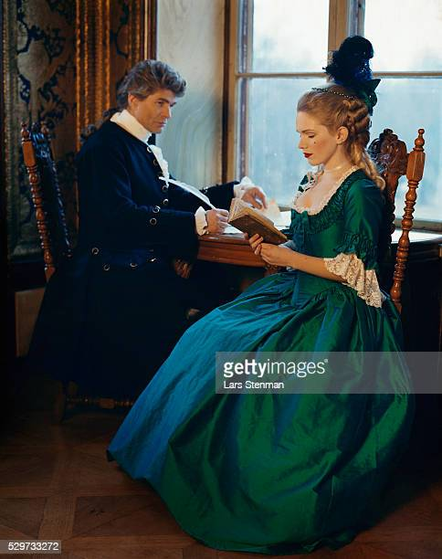 Man and woman in period costumes reading and writing