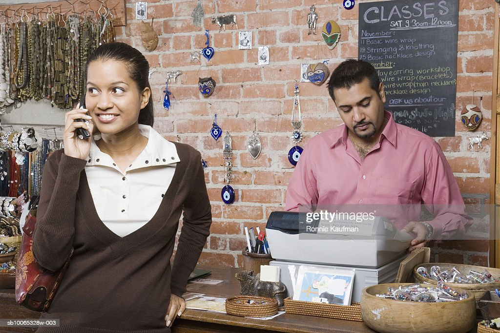 Man and woman in shop, woman using mobile phone : Foto stock