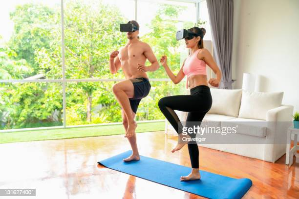 man and woman in sports wear visual radio google workout at home. couple exercising together. - google stock pictures, royalty-free photos & images