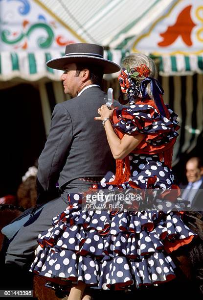 Man and woman in traditional costumes on horseback at the Feria de Abril Seville Andalusia Spain