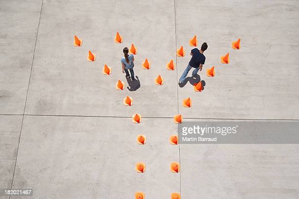man and woman in traffic cones moving apart - relationship difficulties stock pictures, royalty-free photos & images