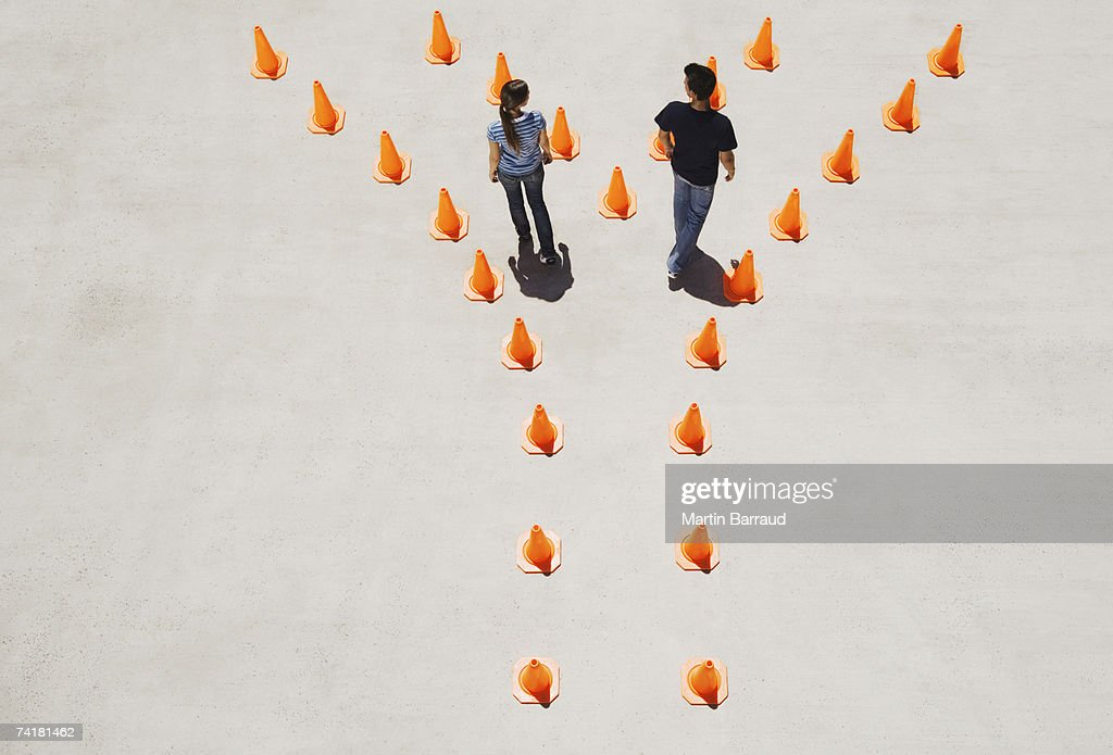 Man and woman in traffic cones moving apart : Stock Photo