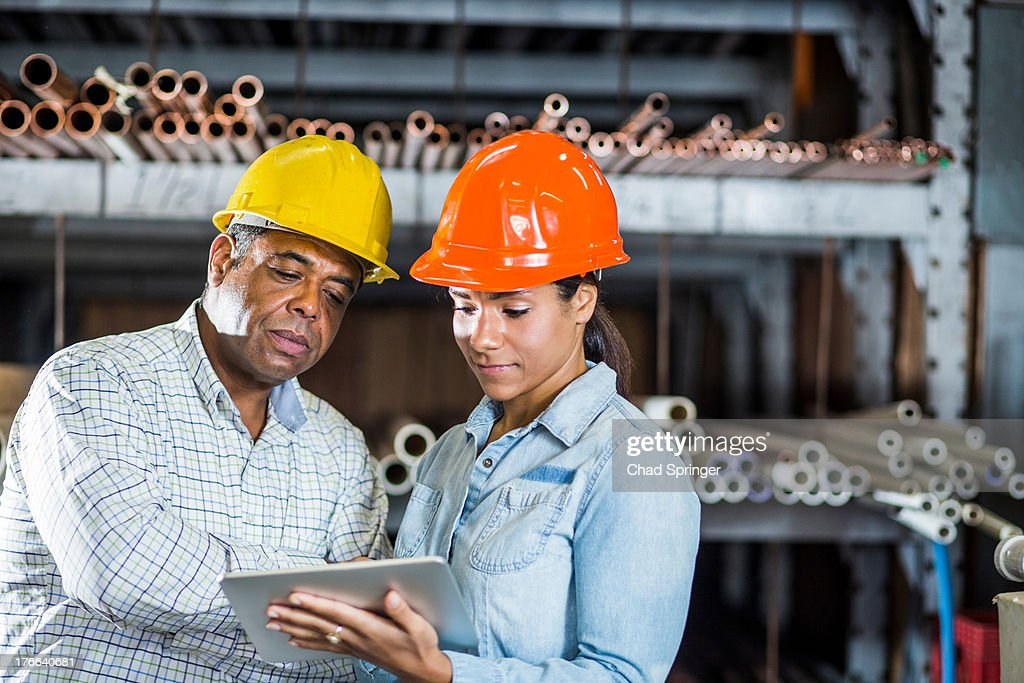 Man and woman in warehouse looking at digital tablet : Stock Photo