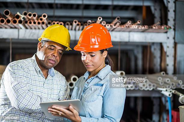 man and woman in warehouse looking at digital tablet - metallic look stock pictures, royalty-free photos & images