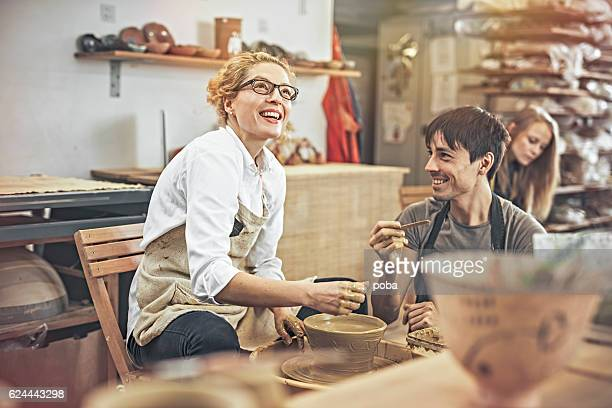 man and woman in workshop working on pottery wheel - pottery stock pictures, royalty-free photos & images