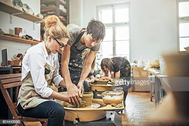 man and woman in workshop working on pottery wheel - ceramic stock photos and pictures