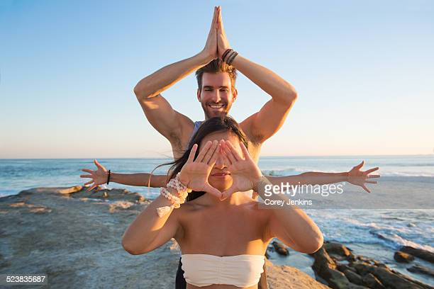 Man and woman in yoga poses, Windansea beach, La Jolla, California