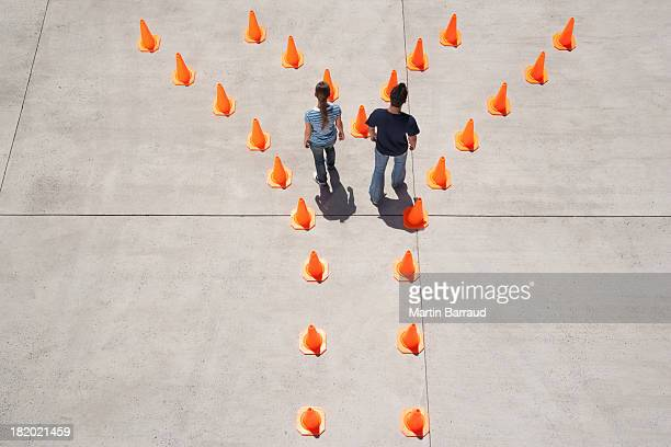 Man and woman inside traffic cones
