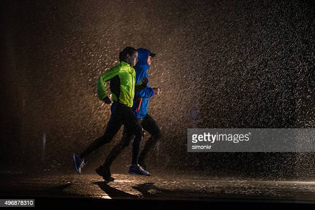 man and woman jogging in city - hood clothing stock photos and pictures