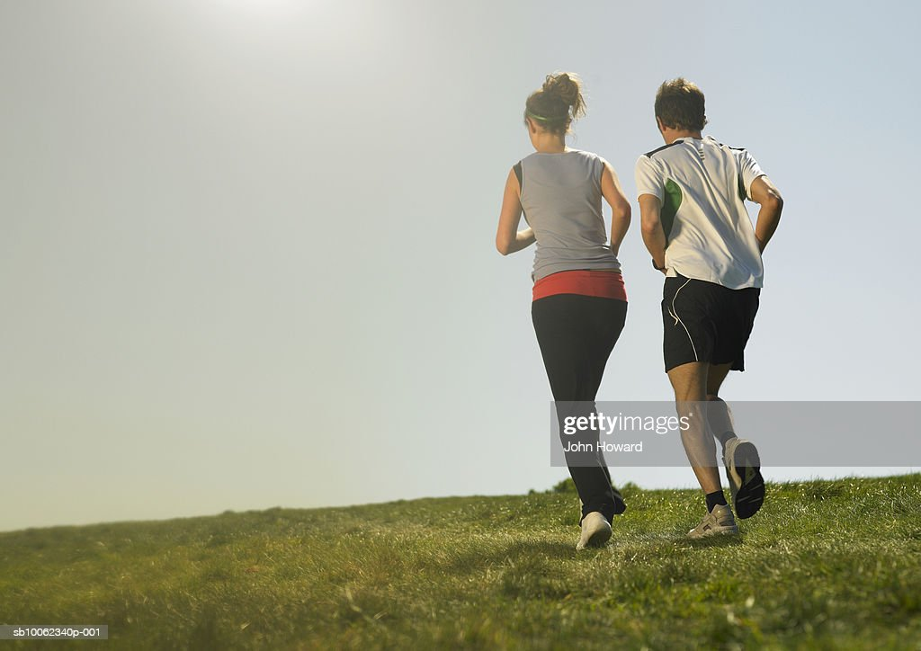 Man and woman jogging on grass, rear view : Stock Photo