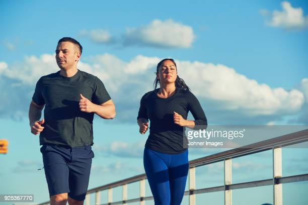 man and woman jogging - all weather running track stock pictures, royalty-free photos & images