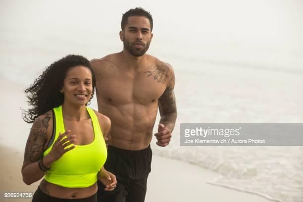 Man and woman jogging together on coastal beach and looking at camera, Hampton, New Hampshire, USA