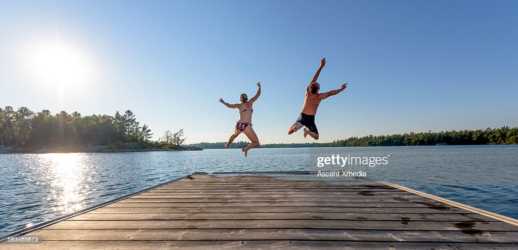 Man and woman jump off boat dock, expressively : Stock Photo