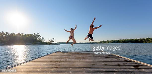 Man and woman jump off boat dock, expressively